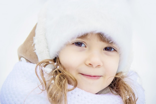 A child plays in the snow in the winter. selective focus.