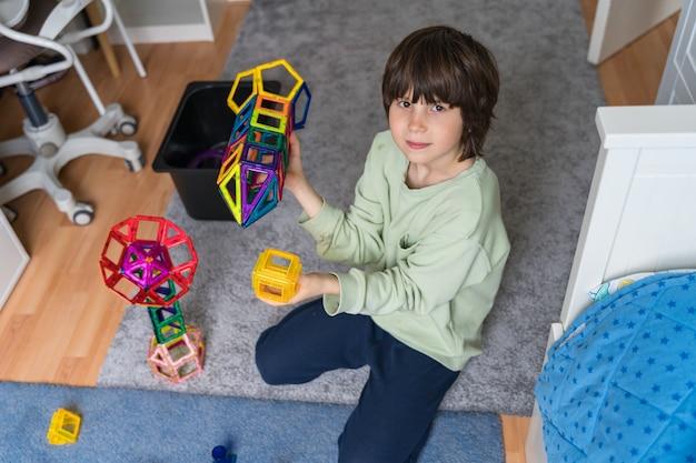 어린이는 침실에서 자기 생성자로 재생합니다.