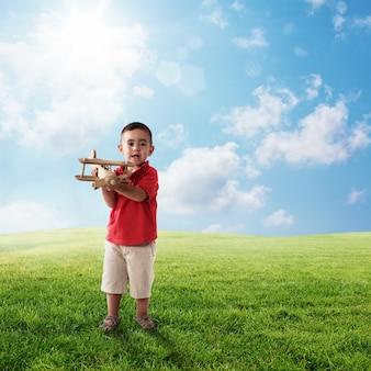 子供は旅行を夢見ている風景の中で木製の飛行機で遊ぶ