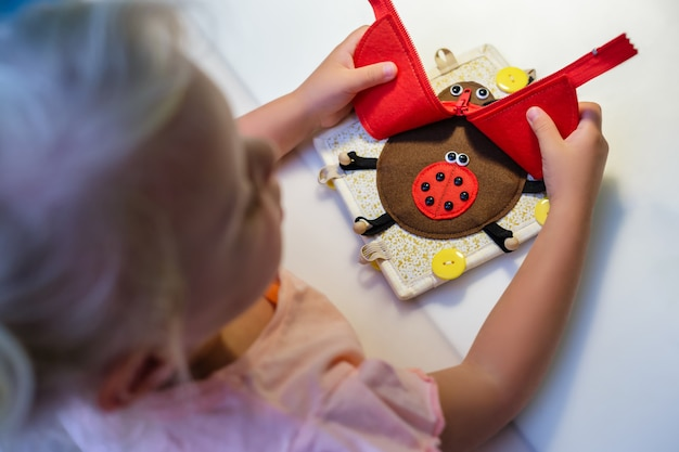 A child plays with an educational toy red ladybug made of felt montessori concept early education