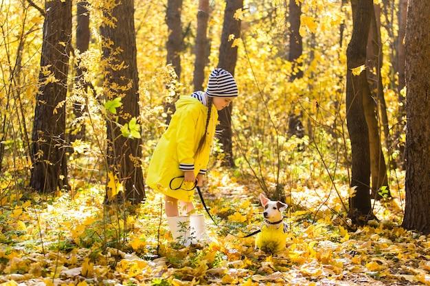 子供は犬の子供とペットと一緒に秋の森の秋の散歩でジャックラッセルテリアと遊ぶ