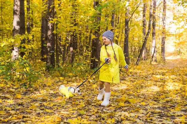 아이 가을 숲에서 잭 러셀 테리어와 함께 재생합니다. 개, 어린이 및 애완 동물과 함께 가을 산책