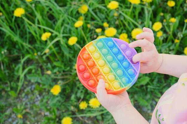 아이는 여러 가지 빛깔의 장난감을 가지고 노는 안티스트레스 팝을 거리에서 팝니다. 배경 복사 공간에 잔디