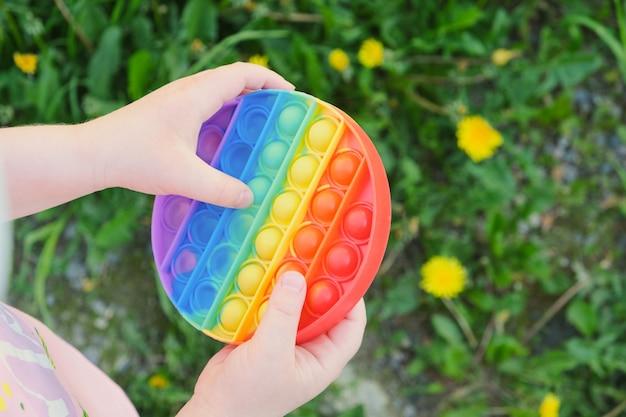 아이는 여러 가지 빛깔의 장난감을 가지고 노는 안티스트레스 팝을 거리에 놓고 잔디를 배경으로 한다