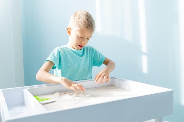 아이는 모래에 그리기, 테이블에 집에서 모래로 재생