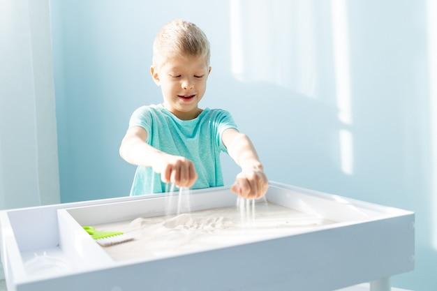 아이는 집에서 탁자 위에 모래를 가지고 놀고, 모래에 그림을 그립니다.