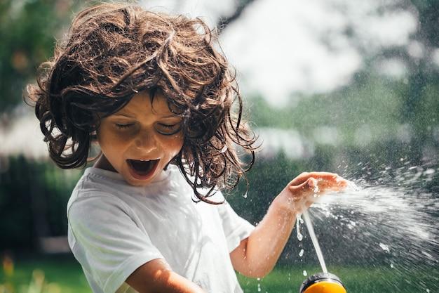 Ребенок играет с водой на заднем дворе в саду