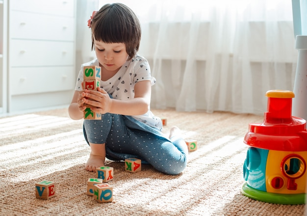 Child plays with  wooden blocks with letters on floor room little girl building tower home kindergarten.