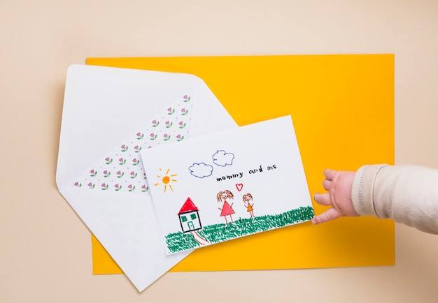 Child pointing finger at drawing of mother and kid