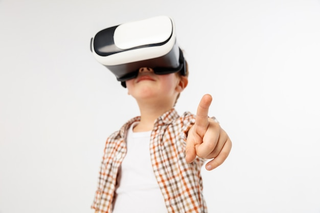 Child pointing to the front with virtual reality glasses isolated