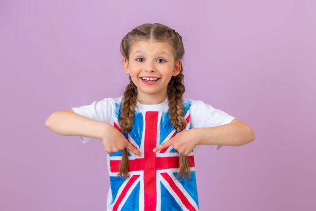 The child points his fingers at the painted english flag on his t-shirt.