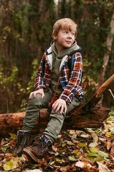 Bambino in posa in natura mentre è seduto su un tronco d'albero