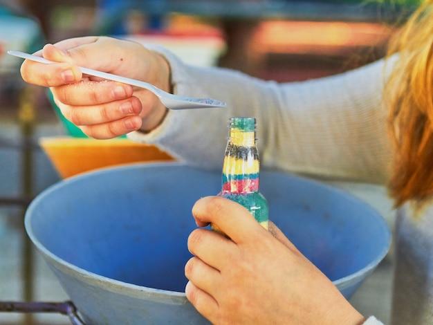 아이는 병에 색깔의 모래를 붓습니다. 공원에서 주간 활동.