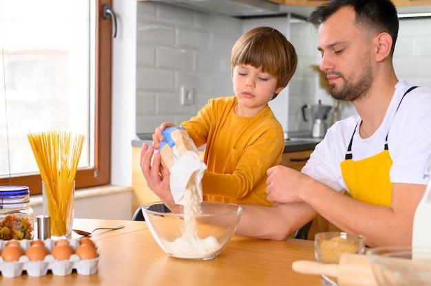子供はボウルに小麦粉を注ぐ