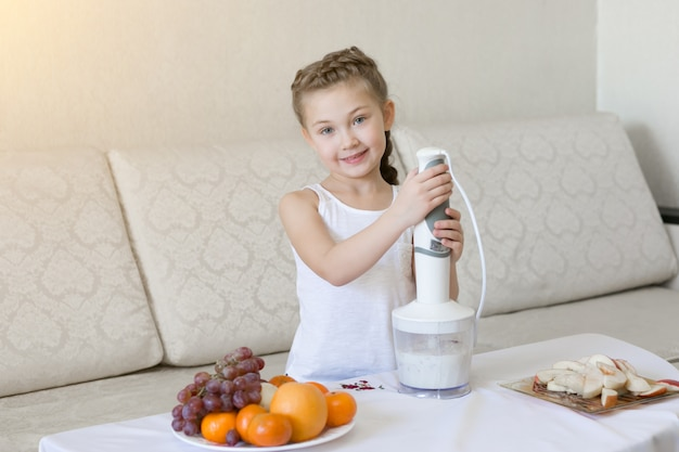The child prepares a cocktail in a blender.
