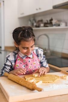 Ребенок готовит печенье и вырезает из раскатанного теста фигурки в виде сердца. руки ребенка делают печенье из сырого теста в форме сердца, крупным планом.