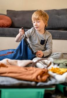 Ребенок готовит багаж дома для путешествия