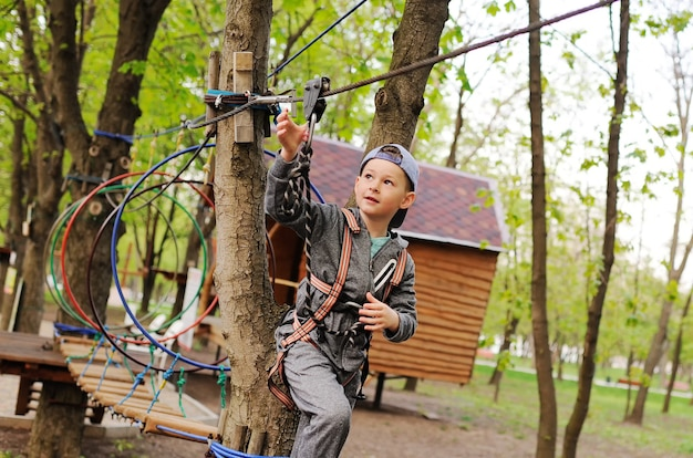 Child preschooler boy is an obstacle in a safety alpinism equipment high rope course