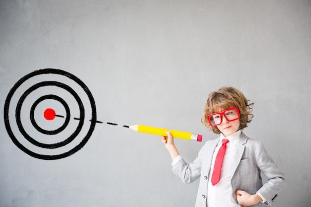 子供はビジネスマンのふりをします。家で遊んでいる子供。想像力、アイデア、スタートアップのコンセプト。学校に戻る