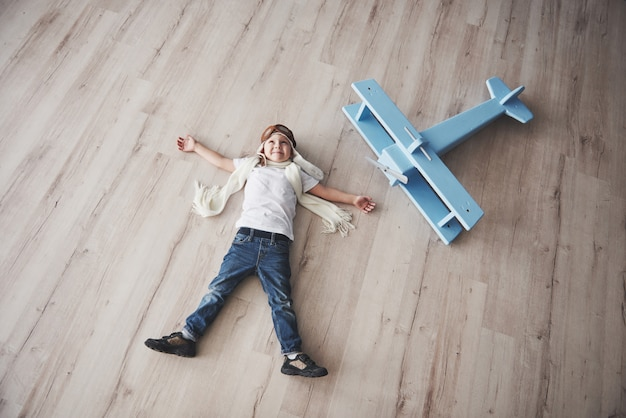子供はパイロットのふりをします。家で楽しんでいる子供。夏休みと旅行。トップビューの肖像画
