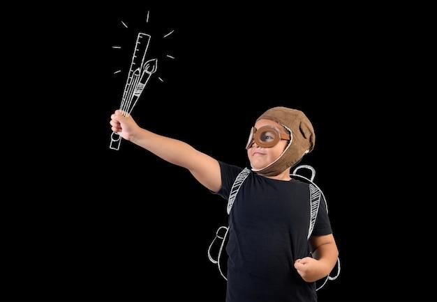 Ребенок притворяется супергероем и держит школьные принадлежности.