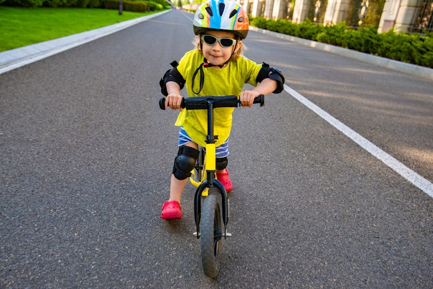 Child in a protective helmet and sunglasses riding a scooter on the road
