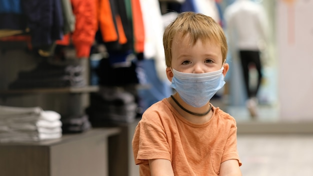 Child in a protective mask in a store