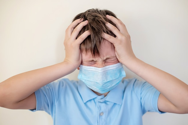 Child in protective medical mask with severe headache squeezed head with hands. boy squinted eyes in pain.