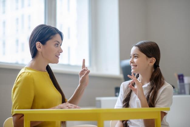 指でサインを勉強しているテーブルに座っている子供の心理学者の気配りのある女性と笑顔の女の子