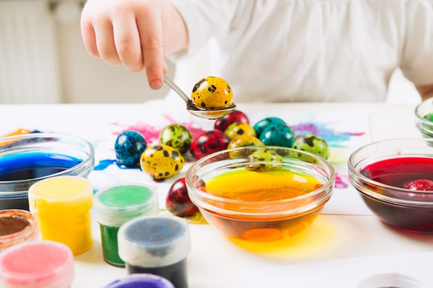 Child pulled yellow quail egg from paint