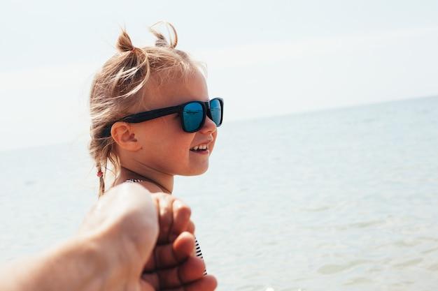 子供は父親を引っ張って海で泳ぎます。