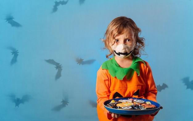 Child in pumpkin carnival costume and medical mask holding a platter of cookies for halloween