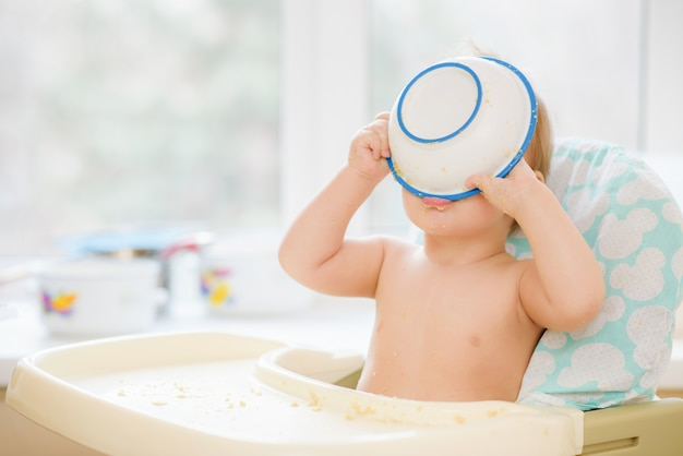 The child put a bowl on his head
