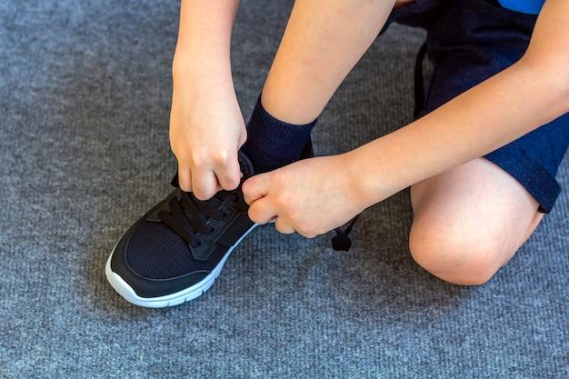 子供はスニーカーを履きました。テキスタイルファッションの黒のスニーカーで少年の足。お子様の流行のカジュアルな服装とストリートファッション。閉じる