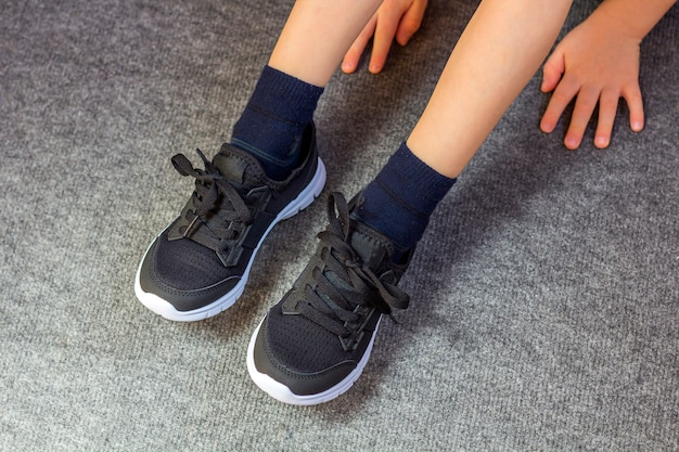 Child put on a pair of sneakers. young boy's legs in textile fashion black sneakers.