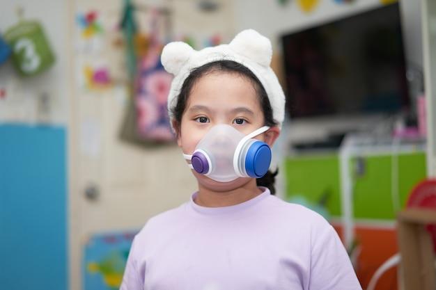 Ребенок надевает защитную маску от covid 19