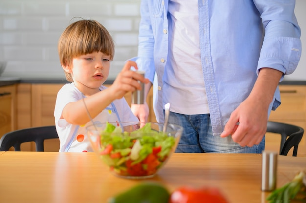 Child puts salt in the salad