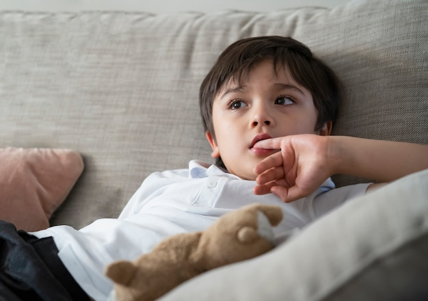 Child putting finger in his mouth. schoolboy biting his finger nails while watching tv, emotional kid portrait, young boy siting on sofa looking out with thinking face or nervous