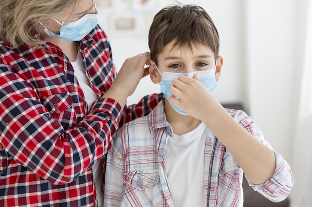 Child putting on medical mask with the help of his mother