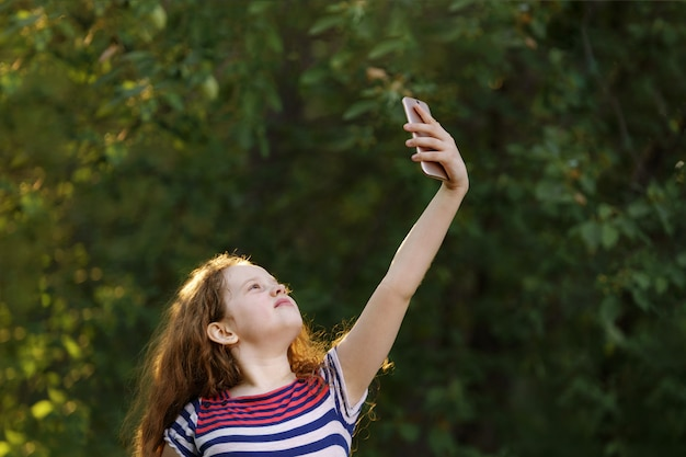 Child raised his hand with smartphone and catches a signal or wi-fi.
