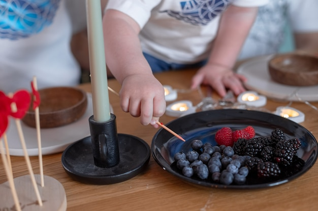 Child reaches for raspberries, blueberries and blackberries on a black plate.