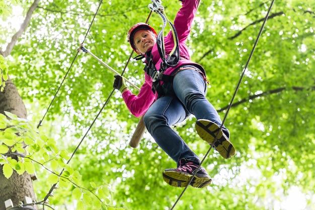 Ребенок достигает платформы, лазая в веревочном курсе
