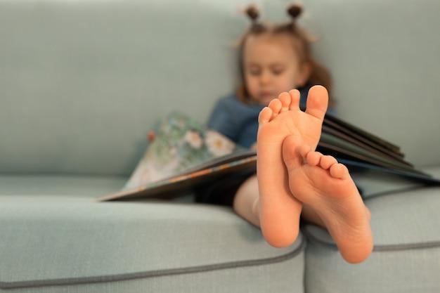 아이는 소파 발에 책을 읽고 지식 교육을 닫습니다. 아이는 잠을 자고 책을 읽는 데 지쳤습니다.