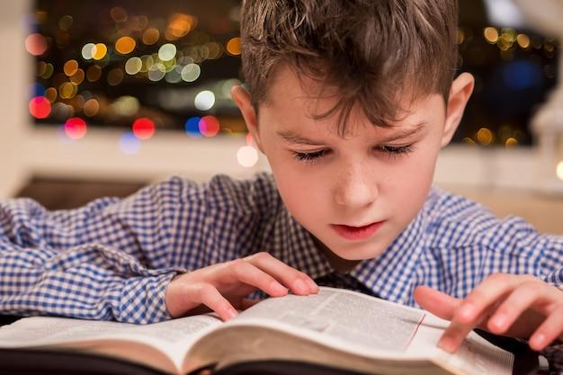 Ребенок читает толстую книгу. мальчик читает книгу у окна. молодой ученик делает домашнее задание. малыш, решающий задачу в книге.