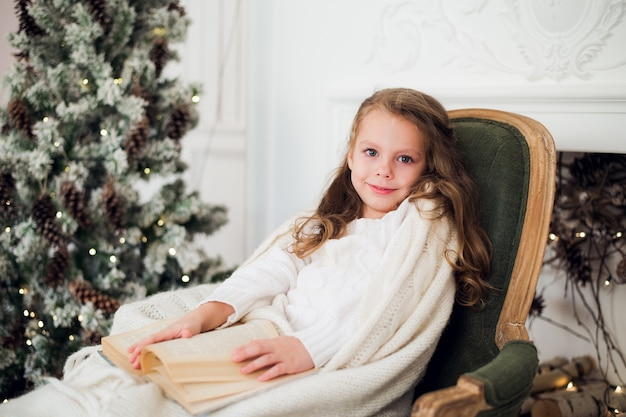 Ребенок, читающий книгу дома на рождество