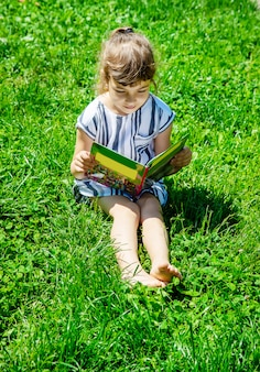 Child reading a book in nature.