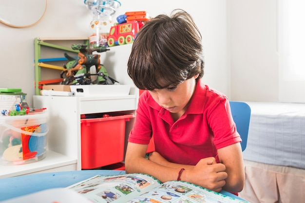 Child reading book at table