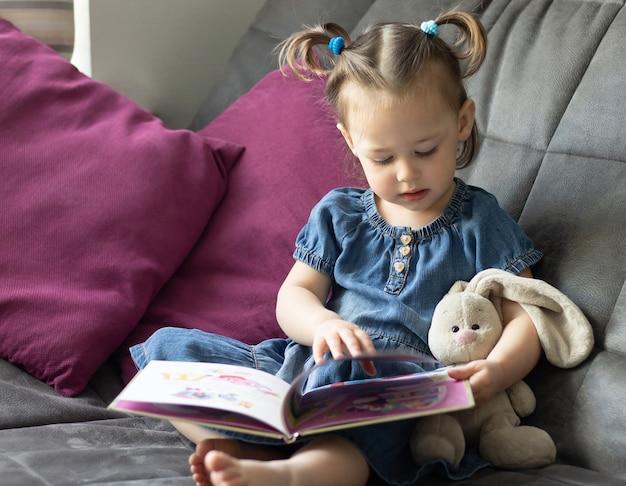 Детское чтение. маленькая милая девочка 1-3 читает книгу с игрушечным плюшевым зайцем, сидящим на диване.