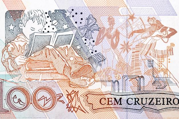 오래된 브라질 돈으로 책을 읽는 아이