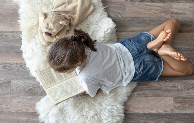 The child reads a book lying on a cozy rug at home with his favorite toy teddy bear.